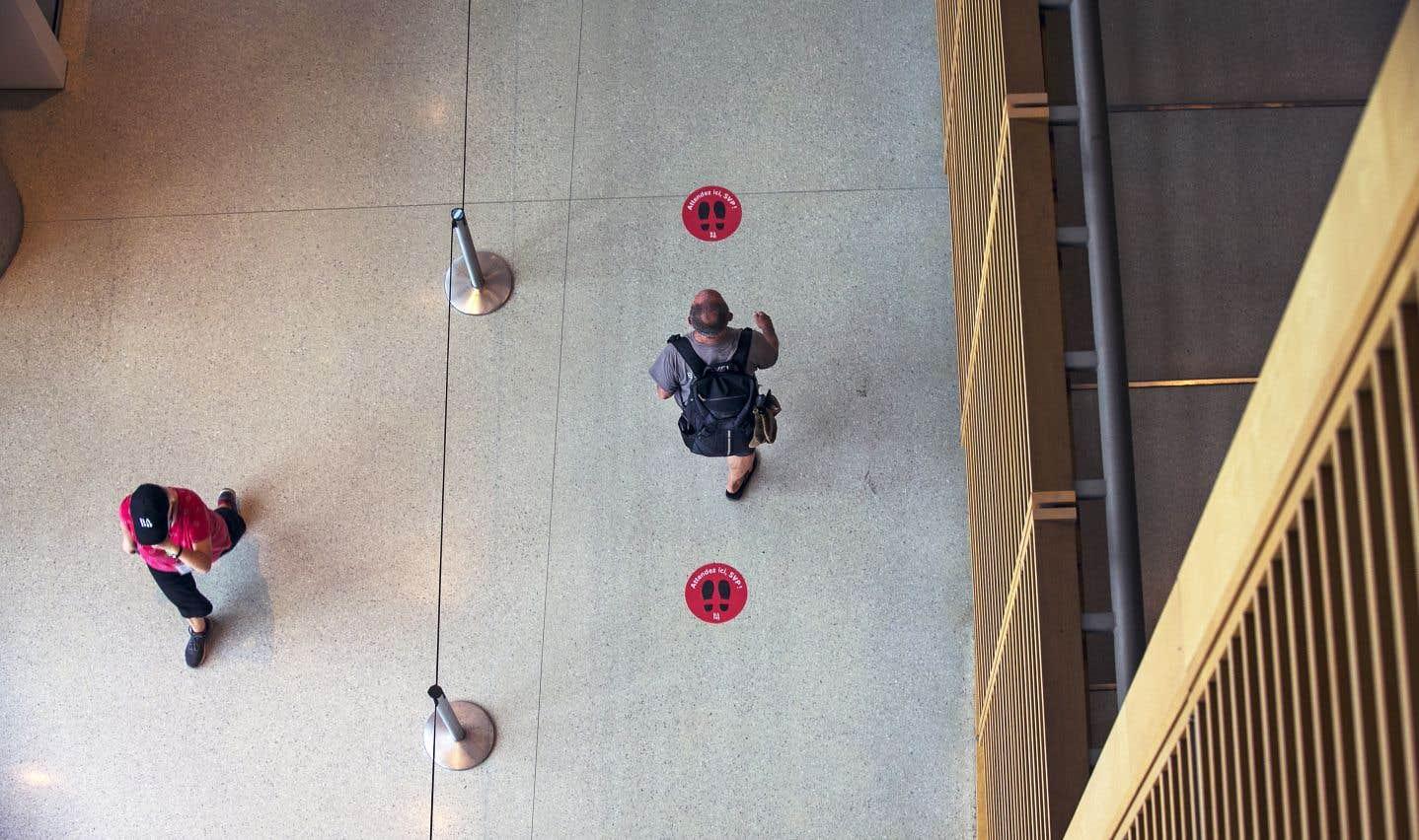 Une nouvelle signalisation indique les distances à maintenir et la direction de la circulation des usagers dans le hall de la Grande Bibliothèque donnant accès au comptoir de prêt.