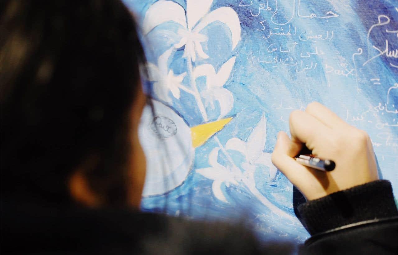 Photo : derrière de la tête et de la main d'une jeune fille aux cheveux bruns. Elle dessine sur un dessin aux teintes bleutées. Il y a des fleurs de lys blanches, formant la tige d'une plante. Aussi des paroles écrite en langue arabe.