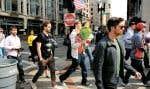 De jeunes gens traversaient la rue en portant des fleurs, mardi, après l'enlèvement des barricades près de l'endroit où s'est produit l'attentat qui a fait 3 morts et 183 blessés lors du marathon de Boston, lundi. Des vigiles ont été tenues en soirée pour rendre hommage aux victimes.