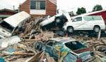 Des voitures et des débris rejetés par le passage d'une vague de tsunami à Dichato, au Chili.