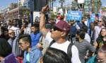 Un manifestant anti-Trump fait un doigt d'honneur à un groupe de partisans du président américain rassemblés au Centre des congrès de San Diego, en mai 2016.