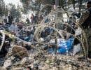 Devant des barbelés, des policiers macédoniens surveillaient jeudi des migrants de différents pays qui ne peuvent entrer sur le territoire.